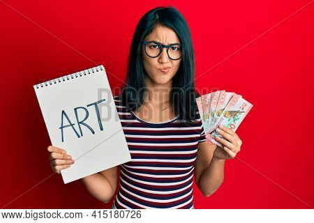 Beautiful asian young woman holding art notebook and 100 new zealand dollars skeptic and nervous, frowning upset because of problem. negative person.