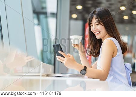 Asian Woman Using Smart Mobile Phone For Online Shopping In Modern Coffee Shop, Holding And Drinking