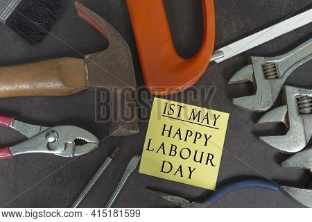 Labour Day Text On Yellow Notepad With Repair Equipment And Many Handy Tools On A Dark Background