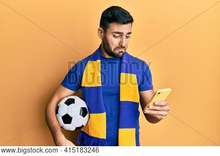 Young hispanic man football hooligan holding soccer ball using smartphone depressed and worry for distress, crying angry and afraid. sad expression.