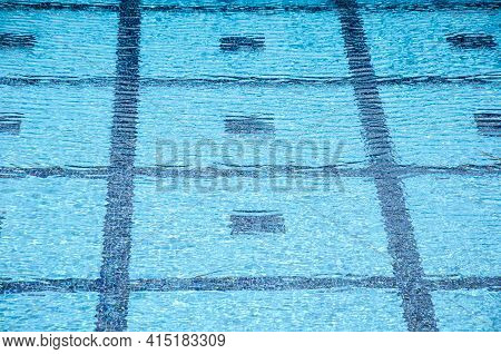 Lined Pool Bottom Through Clear Blue Water. Clear Swimming Pool With Transparent Water. Water Sports