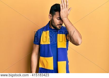 Young hispanic man football hooligan cheering game surprised with hand on head for mistake, remember error. forgot, bad memory concept.