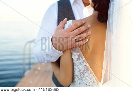 The Groom Hugs The Bride On The Pier Against The Backdrop Of The River At Sunset. Wedding Day Bride