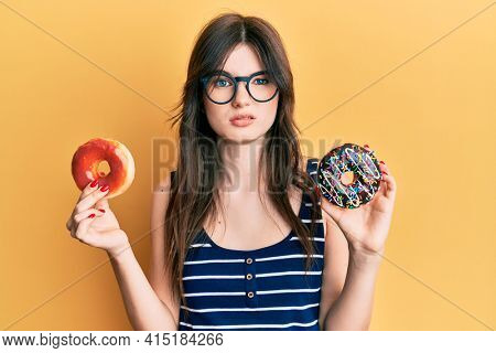 Young beautiful caucasian girl holding tasty colorful doughnuts skeptic and nervous, frowning upset because of problem. negative person.