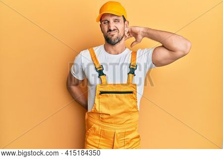Young handsome man wearing handyman uniform over yellow background suffering of neck ache injury, touching neck with hand, muscular pain