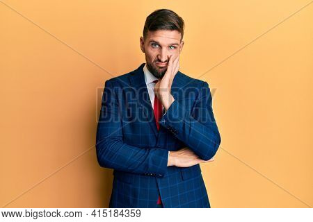 Handsome man with beard wearing business suit and tie thinking looking tired and bored with depression problems with crossed arms.