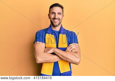 Handsome man with beard football hooligan cheering game happy face smiling with crossed arms looking at the camera. positive person.