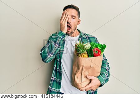 Handsome man with beard holding paper bag with groceries yawning tired covering half face, eye and mouth with hand. face hurts in pain.