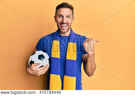 Handsome man with beard football hooligan cheering game holding ball pointing thumb up to the side smiling happy with open mouth