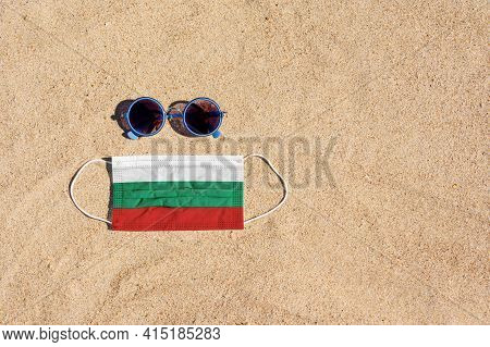 A Medical Mask In The Color Of The Bulgaria Flag Lies On The Sandy Beach Next To The Glasses. The Co