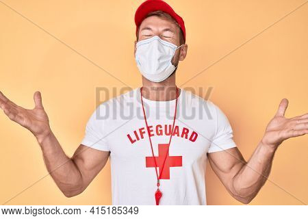 Young caucasian man wearing lifeguard t shirt using medical mask celebrating mad and crazy for success with arms raised and closed eyes screaming excited. winner concept