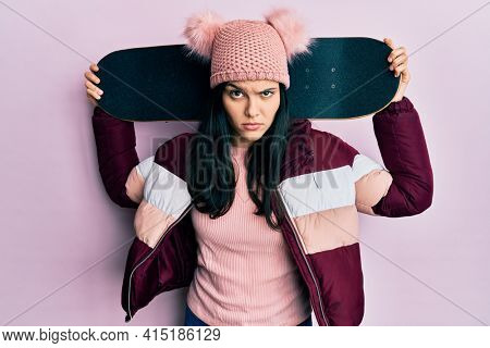 Young hispanic woman holding skate skeptic and nervous, frowning upset because of problem. negative person.