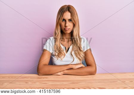 Beautiful blonde young woman wearing casual clothes sitting on the table skeptic and nervous, frowning upset because of problem. negative person.