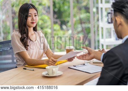 Young Asian Woman Graduate Holding And Submitting The Resume Document To Two Manager Before Start To