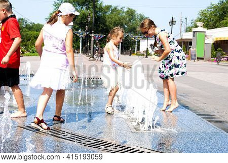 Happy Little Girl Plays With Water Near The Fountain. Hot Summer Day. City Park, Street With Fountai