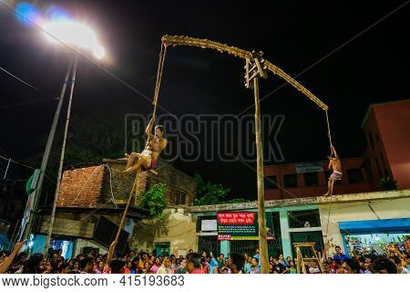 Howrah, West Bengal,india - 15th April 2019: Two Hindu Devotees Are Hanging From Pole In Air, At Nig