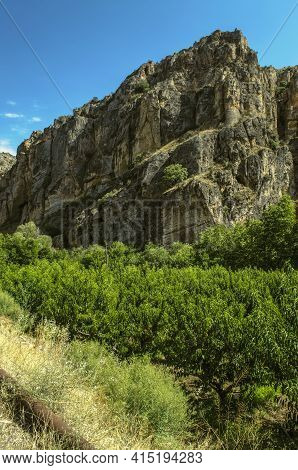 Peach Orchards At The Foot Of A Ridge Of Large Basalt Rocks Near The Road Leading To The City Of Yeg