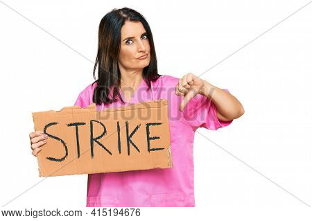 Middle age brunette doctor woman holding strike banner cardboard with angry face, negative sign showing dislike with thumbs down, rejection concept