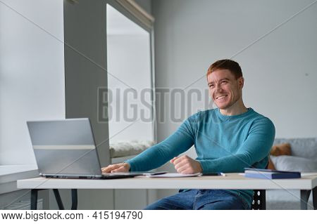 Man Is At Home At His Desk Uses A Laptop Smiling And Showing A Like To His Colleague Via Video Commu
