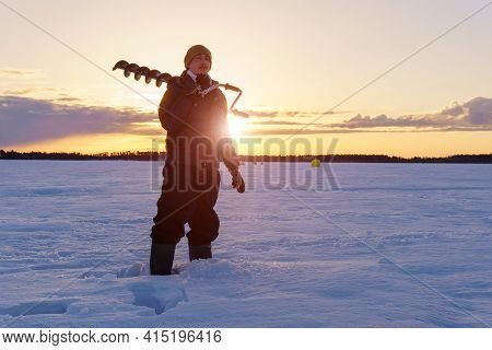 Winter Fishing. Young Man Fisherman With A Drill For Ice Fishing. Sunrise