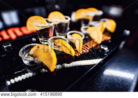 9 Shot Glasses With Clear Alcohol, With Salt And Slice Of Lemon On The Edge Of The Shot Glass. All T