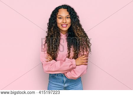 Young hispanic woman with curly hair wearing casual sweatshirt happy face smiling with crossed arms looking at the camera. positive person.