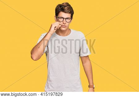 Handsome caucasian man wearing casual clothes and glasses mouth and lips shut as zip with fingers. secret and silent, taboo talking