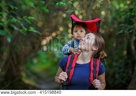 Mother With Toddler Child In Backpack Carrier Is Walking In Forest. Tourist Is Carrying A Baby On Hi