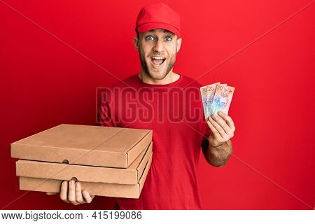 Young caucasian man holding delivery box and swiss franc banknotes celebrating crazy and amazed for success with open eyes screaming excited.