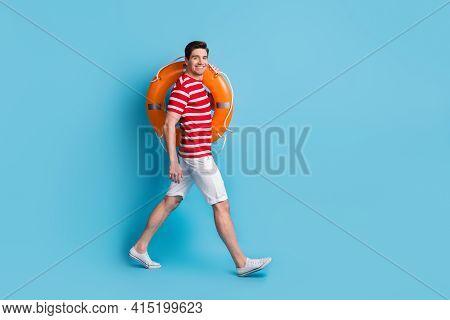 Full Body Profile Side Photo Of Happy Man Hold Orange Lifesaver Ring Go Copyspace Isolated On Blue C