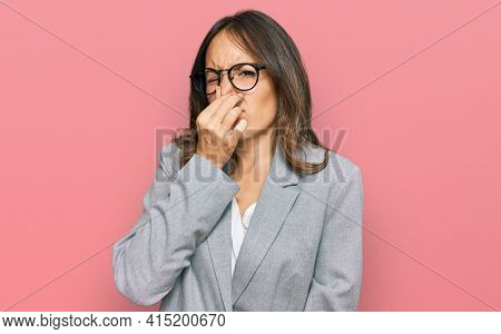 Young brunette woman wearing business clothes smelling something stinky and disgusting, intolerable smell, holding breath with fingers on nose. bad smell