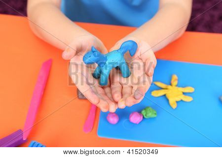 Holding-handgemachten Plastilin Pferdewagen über Schreibtisch des Kindes-Hände