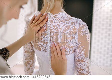 The Bridesmaid Helps The Bride Get Ready For Her Wedding Day And Put On A White Wedding Dress. Back