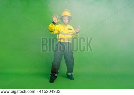 Full Length Photo Of Confident Serious Young Fire Lady Workwear Yellow Helmet Choking Flame Fog Isol