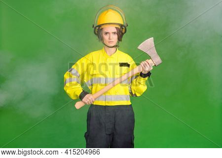 Photo Of Pretty Serious Young Firewoman Dressed Yellow Uniform Helmet Holding Hatchet Isolated Green