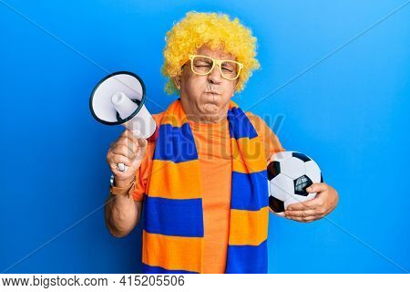 Senior hispanic man football hooligan cheering game holding ball and megaphone puffing cheeks with funny face. mouth inflated with air, catching air.
