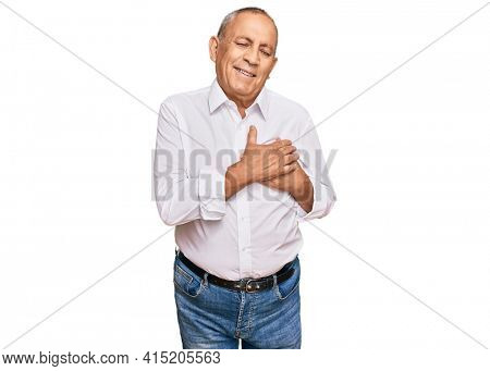 Handsome senior man wearing elegant white shirt smiling with hands on chest with closed eyes and grateful gesture on face. health concept.