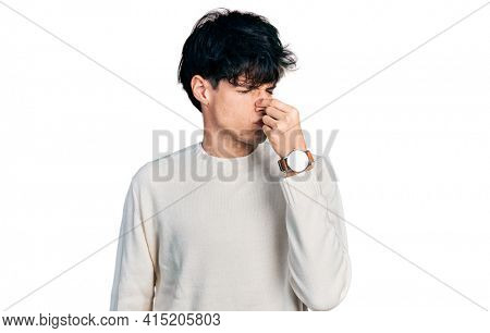 Handsome hipster young man wearing casual winter sweater smelling something stinky and disgusting, intolerable smell, holding breath with fingers on nose. bad smell