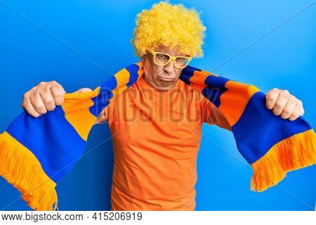 Senior hispanic man football hooligan cheering game skeptic and nervous, frowning upset because of problem. negative person.
