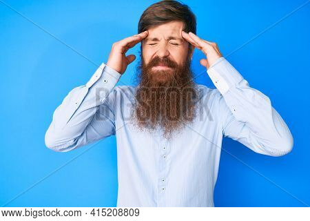 Handsome young red head man with long beard wearing elegant clothes with hand on head, headache because stress. suffering migraine.