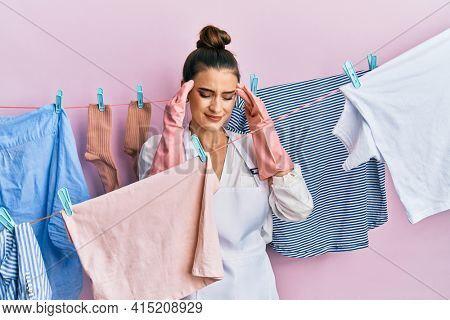 Beautiful brunette young woman washing clothes at clothesline with hand on head for pain in head because stress. suffering migraine.