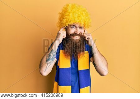 Redhead man with long beard football hooligan cheering game wearing funny wig covering ears with fingers with annoyed expression for the noise of loud music. deaf concept.