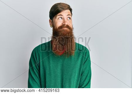 Redhead man with long beard wearing casual clothes smiling looking to the side and staring away thinking.
