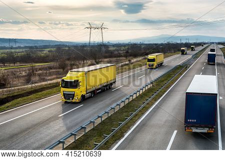Convoys Or Caravans Of Transportation Trucks Passing On A Highway On A Bright Blue Day. Highway Tran