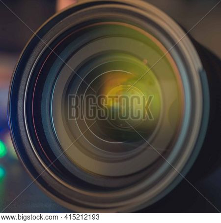The photo or videocamera lens on dark background with lense reflections