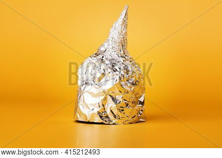 Hat Made Of Aluminium Foil On Yellow Background. Used By Those Who Are Afraid Of 5g Radiation Or Ali