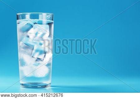 A Glass With Ice And Clean Water On A Blue Background.