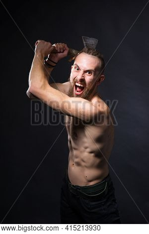 A Brutal Man With A Long Beard And Mustache With An Ax As A Viking Swung To Strike In The Studio On