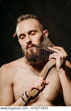 Young Handsome Man With A Thick Beard And Large Mustache Shaves His Beard With An Ax In The Studio O