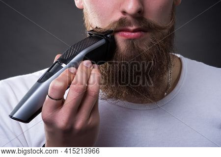 Young Handsome Bearded Man Shaves Thick Beard With Trimmer In Studio Close-up